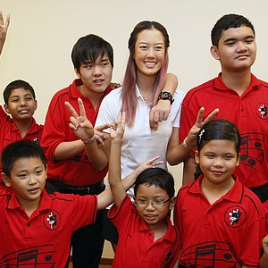 Golfer Michelle Wie, center, of the United States poses with autistic children at Creative Arts Centre for autistic children during its launch in Shah Alam, outside Kuala Lumpur, Malaysia, Monday, Oct. 8, 2012.