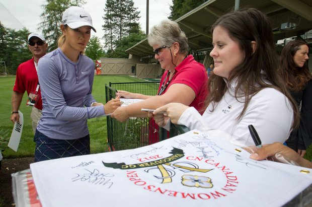 Michelle Wie signs autographs after practicing for the LPGA Tour's Canadian Women's Open golf tournament at Vancouver Golf Club in Coquitlam, British Columbia, on Tuesday, Aug. 21, 2012.