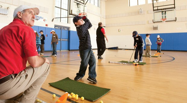 Dave Robinson (left), who owns several TGA franchises in Michigan, brings golf instruction to schools.