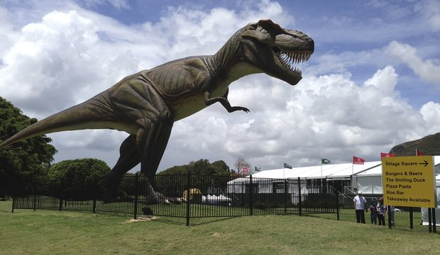 People stand near an 26-foot replica of a T-Rex standing between the 9th green and the 10th tee at the Sunshine Coast resort course in south Queensland, Australia, Tuesday, Dec. 11, 2012. The Australian PGA will move from its Sunshine Coast resort course location after 11 years, with blame lying indirectly, on the new robotic dinosaur.