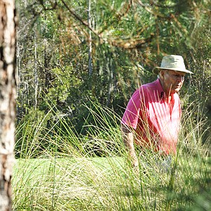 Arnold Palmer searches for his lost ball after his tee shot at No. 7 during the first round of the Father/Son Challenge at the Ritz-Carlton Golf Club in Orlando.