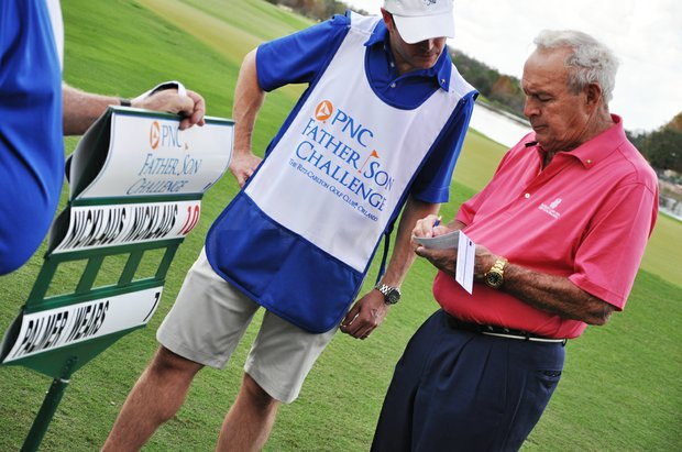 Arnold Palmer checks his scorecard after the first round of the Father/Son Challenge at the Ritz-Carlton Golf Club in Orlando.