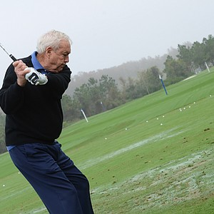 Arnold Palmer hits on the range before the start of the Father/Son Challenge at the Ritz-Carlton Golf Club in Orlando.