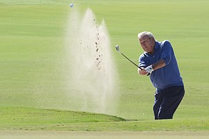 Arnold Palmer hits out of a bunker at the par-5 3rd hole during the first round of the Father/Son Challenge at the Ritz-Carlton Golf Club in Orlando.
