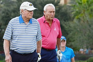 Jack Nicklaus and Arnold Palmer survey birdie putts on the 18th green at the Father/Son Challenge at the Ritz-Carlton Golf Club in Orlando.