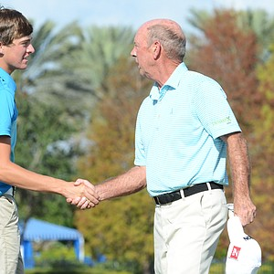 Taylor Funk (left) shakes hands with three-time major winner Larry Nelson on the 18th green during the Father/Son Challenge at the Ritz-Carlton Golf Club in Orlando.