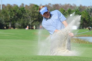 Fred Funk hits out of a bunker in front of the 18th green during the Father/Son Challenge at the Ritz-Carlton Golf Club in Orlando.