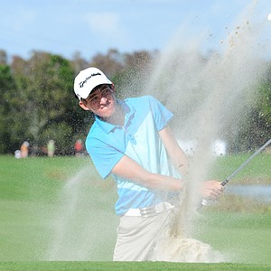 Taylor Funk hits out of a bunker in front of the 18th green during the Father/Son Challenge at the Ritz-Carlton Golf Club in Orlando.