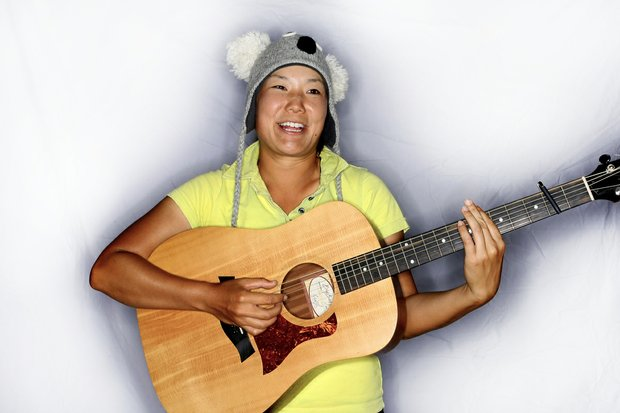Tiffany Joh with her hats and guitar, two of her favorite things while traveling.