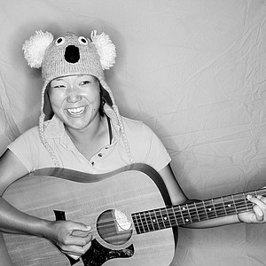 "Tiffany Joh with her unique ""beanie"" hats and her musical talent with the guitar."