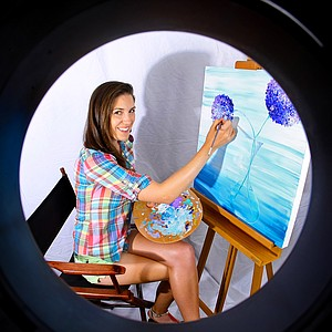 Sandra Gal seen through a ring flash tube as she works on her latest painting.