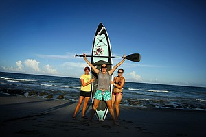 Stacy Lewis shows off her paddle boarding skills she hones in her off time. Here she and friends Alison Walshe, center, and Cindy LaCrosse, right, pose on the beaches in Jupiter.