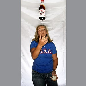 Angela Stanford showing off her love for the Texas Rangers and her skill of juggling and drinking her favorite drink Dr. Pepper.