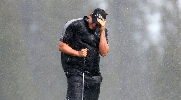 Scott Stallings shields himself from the wind and rain as he attempts to putt on the second hole green during the first round of the Hyundai Tournament of Champions at the Plantation Course on January 4, 2013 in Kapalua, Hawaii.