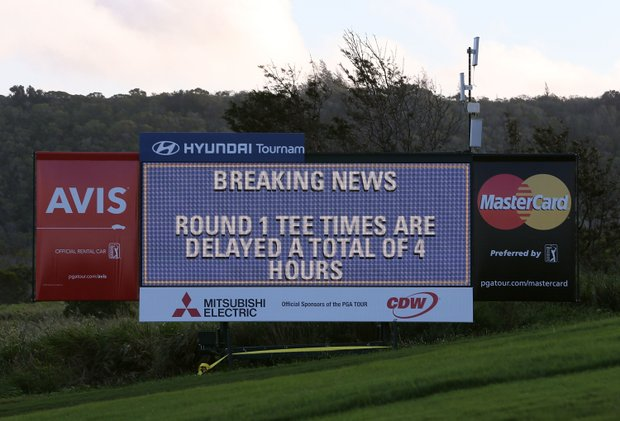 A scoreboard displays the 4-hour delay notification before the replay of the first round of the Hyundai Tournament of Champions at the Plantation Course on Sunday.