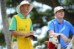 Russell Henley and his caddie talk over his shot before he tees off on the 4th hole during the third round of the Sony Open.