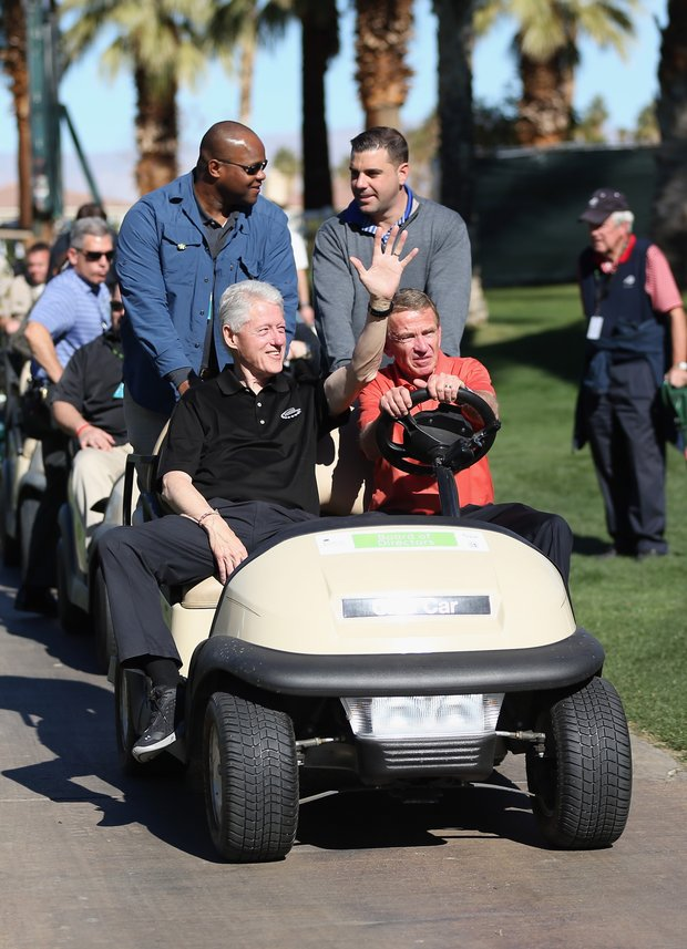 Former President Bill Clinton waves to fans as he's driven around the course by PGA Tour Commissioner Tim Finchem during the first round of the Humana Challenge.