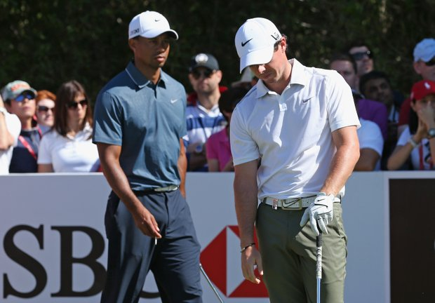 Rory McIlroy reacts to a poor shot as Tiger Woods looks on during the second round of The Abu Dhabi HSBC Golf Championship.