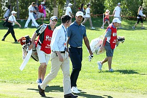 Tournament official Miguel Vidaor chats to Tiger Woods during the second round of The Abu Dhabi HSBC Golf Championship.