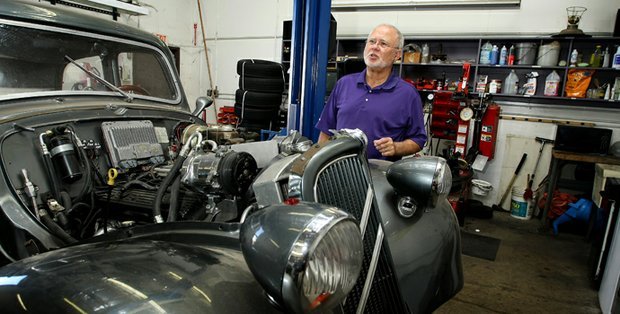 John Solheim poses with one of his father's cars which he is in the process of having restored at the Ping headquarters in Scottsdale, Ariz.