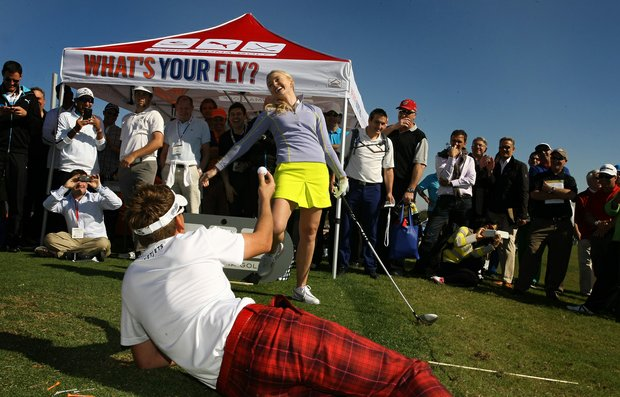 Golf pro Blair O'Neal laughs after Tour star Ian Poulter catches her ball after she attempted a trick shot in the Cobra Puma Golf area at the PGA Merchandise Show's Outdoor Demo Day at Orange County National near Orlando, Fla.