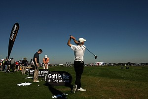 Martin Schlenker of Pennsylvania hits balls  at Demo Day while visiting with fellow classmates from the Penn State PGM program.
