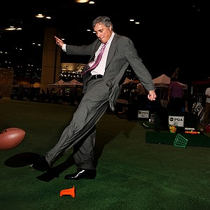 Former NFL kicker, Nick Luckhurst, shows his skills in the hitting bays during the 2013 PGA Merchandise Show. Luckhurst is CEO of American Hole 'N One Inc.