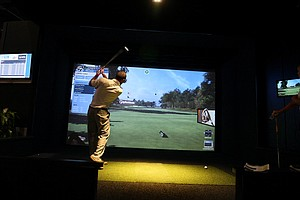 Show attendees take part in the TaylorMade closest to the pin challenge at the Full Swing simulator booth.