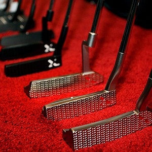 A lineup of putters is on display at Tour Edge on the show floor.