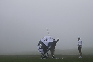 Vijay Singh warms up for the fog-delayed start to the third round of Farmers Insurance Open golf tournament, Saturday, Jan. 26, 2013, in San Diego.
