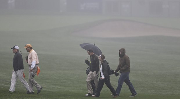 Golf fans cross a fairway in the fog at Torrey Pines golf course during a weather delay before the start of the third round of the Farmers Insurance Open golf tournament Saturday, Jan. 26, 2013, in San Diego.