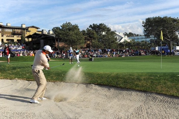 Tiger Woods hits from a bunker on No. 18 during the first round of the Farmers Insurance Open.