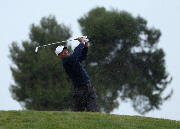 Tiger Woods hits out of a fairway bunker on No. 8 during the second round of the Farmers Insurance Open.