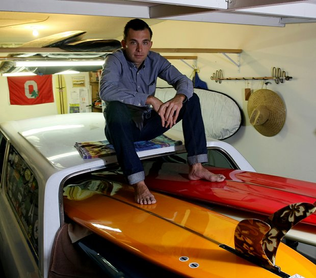 Philip Foster, tour rep with Mitsubishi Rayon poses with some of his surfboards at his home in his garage in Encinitas, Calif.
