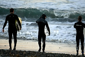 TaylorMade Golf co-workers prepare to head into very cold water left to right Michael Hesterberg, Christopher Piniarski and Scott Mayers while surfing at South Ponto State Beach in Carlsbad area near San Diego, CA.