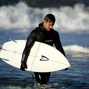 Christopher Piniarski of TaylorMade leaves the beach after surfing at South Ponto State Beach in Carlsbad area near San Diego, CA.