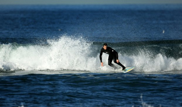 TaylorMade's Michael Hesterberg catches a wave at South Ponto State Beach in Carlsbad area near San Diego, CA.