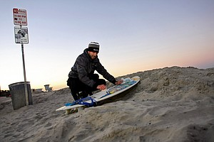 TaylorMade's Scott Mayers prepares his board on a cold morning before surfing at South Ponto State Beach in Carlsbad area near San Diego, CA.