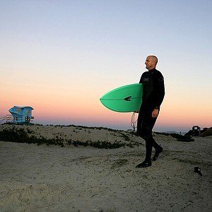 Eric Loper of TaylorMade heads to the water while surfing at South Ponto State Beach in Carlsbad area near San Diego, CA.