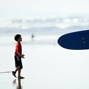 Carl Pettersen of Lamkin Grips meets up with his oldest son Brooks, 5, after surfing in Del Mar area of San Diego.
