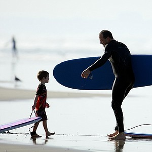 Carl Pettersen of Lamkin Grips greeting his two boys Davis, 4, left, and Brooks, 5, after a morning of surfing in Del Mar area of San Diego.