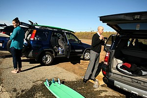 Eric Loper far right of TaylorMade fixes his collar while getting dressed after surfing during lunch break near Carlsbad. At left is Michelle Penney also of TaylorMade.