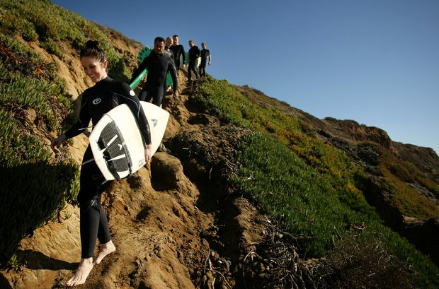 TaylorMade employees Michelle Penney, Maresala Milo, Eric Loper, Dan Barelmann, Josh Dipert and Scott Mayers begin their journey down a steep slope to do a little surfing during lunch break near Carlsbad.