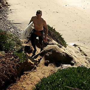 Scott Mayers of TaylorMade heads back up the steep slope after spending his lunch break surfing near Carlsbad.
