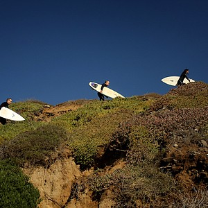 From left to right, Dan Barelmann, Josh Dipert, Michelle Penney and Maresala Milo of TaylorMade make their way back up to their car after surfing during lunch break near Carlsbad.
