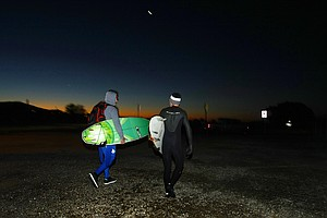 Oakley's Dave Ortley, left, and Gregg Hemphill, right, take a bit of a walk to one of their favorite surfing spots in the Trestles area of San Clemente.