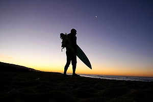 Dave Ortley of Oakley looks over the surf before heading in the freezing waters in the Trestles area of San Clemente.