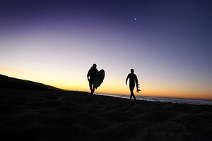 Oakley guys Dave Ortley, left, and Gregg Hemphill, right, take a bit of a walk to one of their favorite surfing areas in the Trestles area of San Clemente.