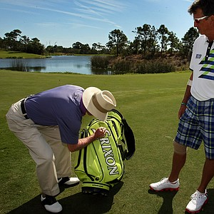 Dana Quigley watches as Tom Kite signs a golf bag that is part of a silent auction during Devon Quigley Pro-Am at the Floridian.