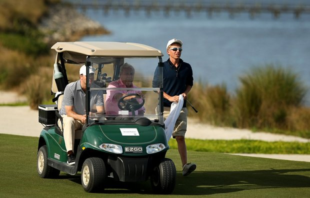 Carson Cavner from a local high school's golf team caddied for Arnold Palmer during the Devon Quigley Pro-Am at the Floridian.